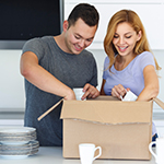 This image shows a young and in love smiling couple unpacking boxes in their new home. They are in the kitchen. We can see plates on the table and they taking cups from the box. In the background we can see kitchen elements.
